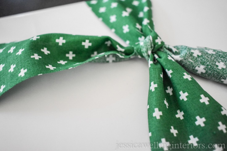 "green fabric ""ribbon"" bow being adjusted"