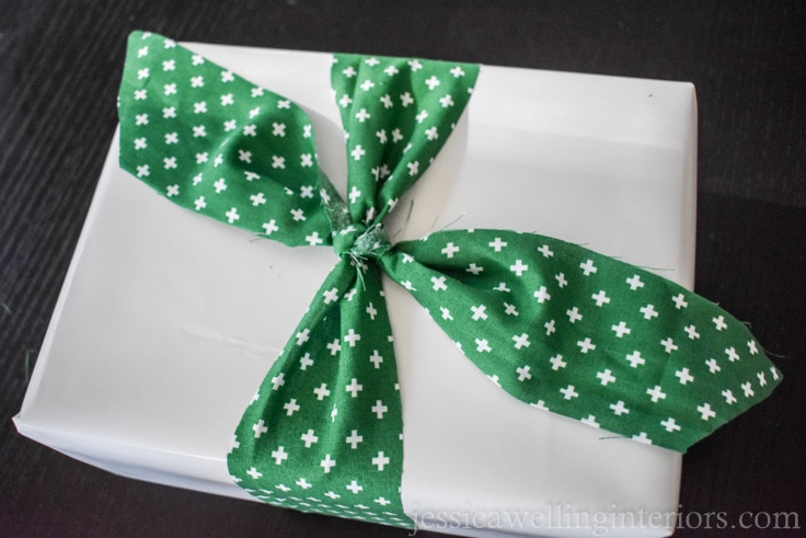 Christmas gift wrapping with white paper and green fabric ribbon
