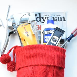 Red Christmas stocking with DIY tool stocking stuffers sticking out the top