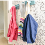 Easy Modern Coat Hooks: Aqua-painted wood coat rack on wall with children's coats and sweaters hanging from it