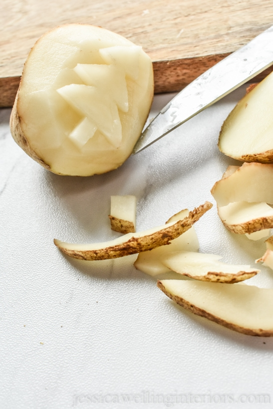 potato being carved into a potato stamp Christmas tree with a pairing knife. Sitting on a wood cutting board