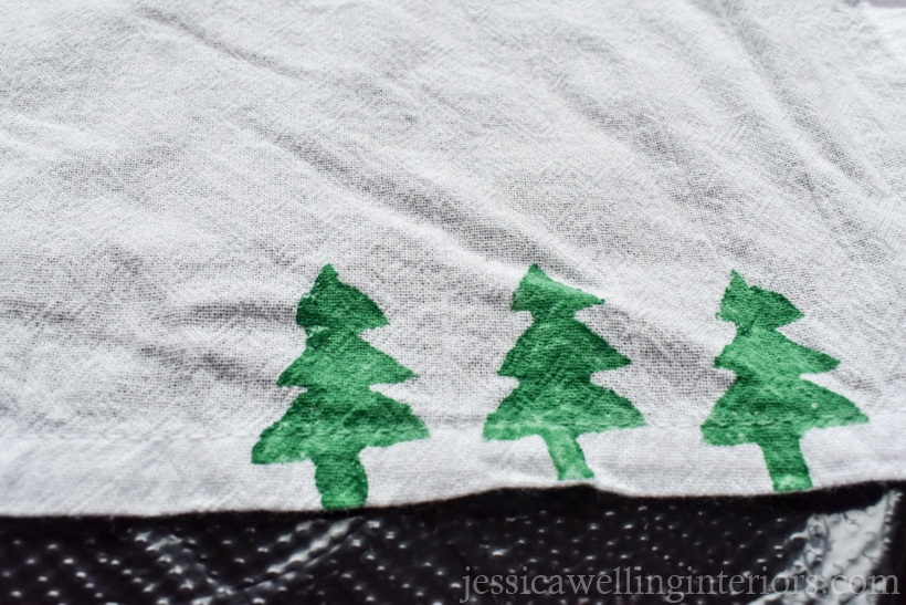 edge of a white tea towel with three green Christmas trees stamped on the bottom
