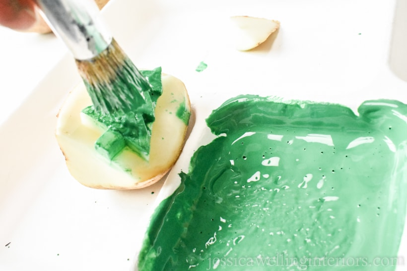 Christmas tree potato stamp being dabbed with green paint using a stencil brush