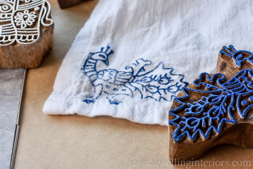 close-up of handmade wood printing block peacock with blue paint on it, and tea towel stamped with the same in the background