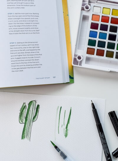 watercolor paint palette, paintbrush, and open workbook