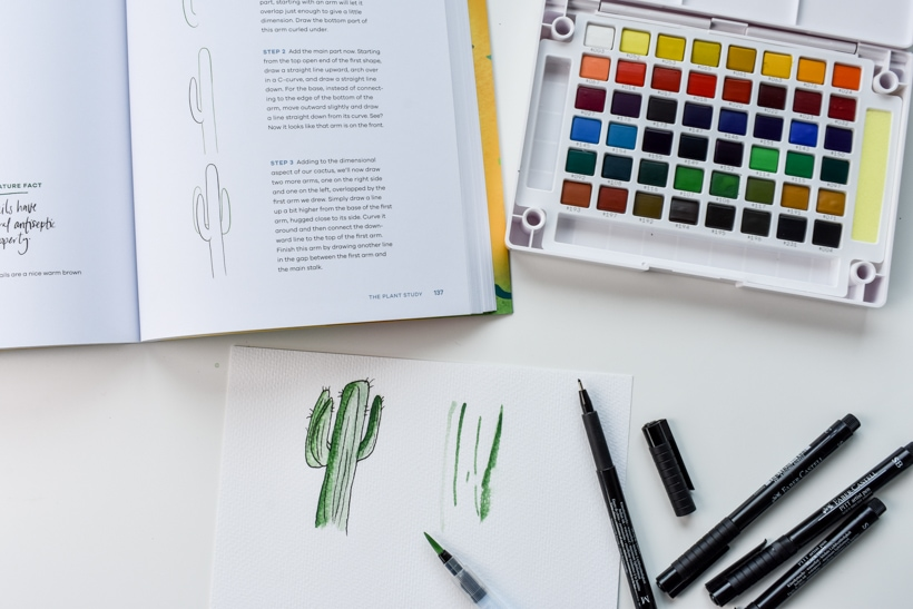 watercolor paint palette next to open workbook and paper with watercolor cactus and black drawing pens gift ideas for women