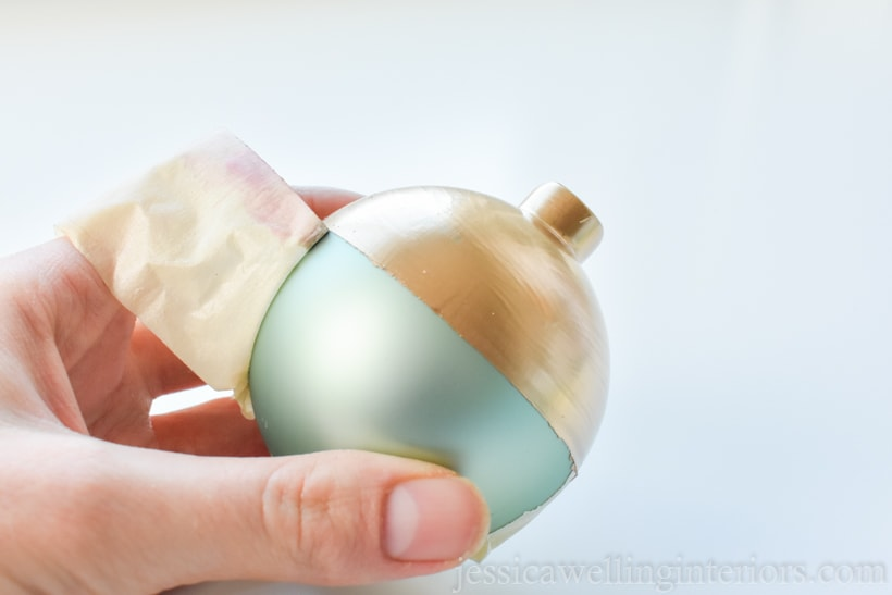 hand holding glass ball ornament and removing masking tape from around the center