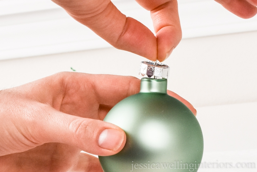 close-up of hands holding a light green glass ball ornament, pulling the metal top off