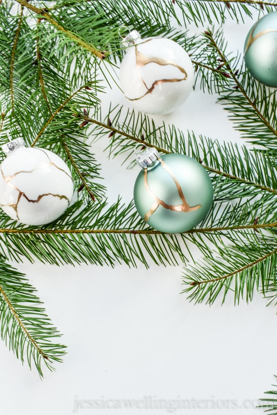 glass ball kintsugi Christmas ornaments with fir branches on a white background