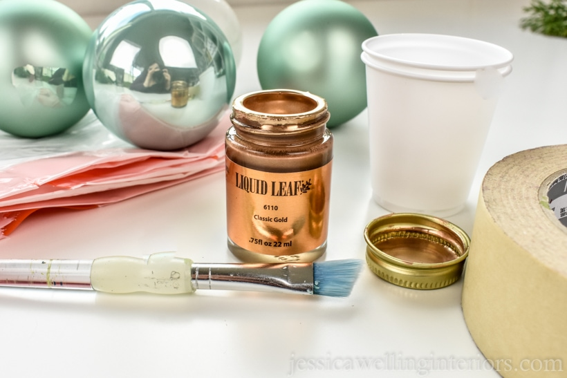 supplies to make DIY Christmas ornaments- glass ball ornaments, gold leaf paint, paint brush, plastic trash bag, masking tape, and dixie cups