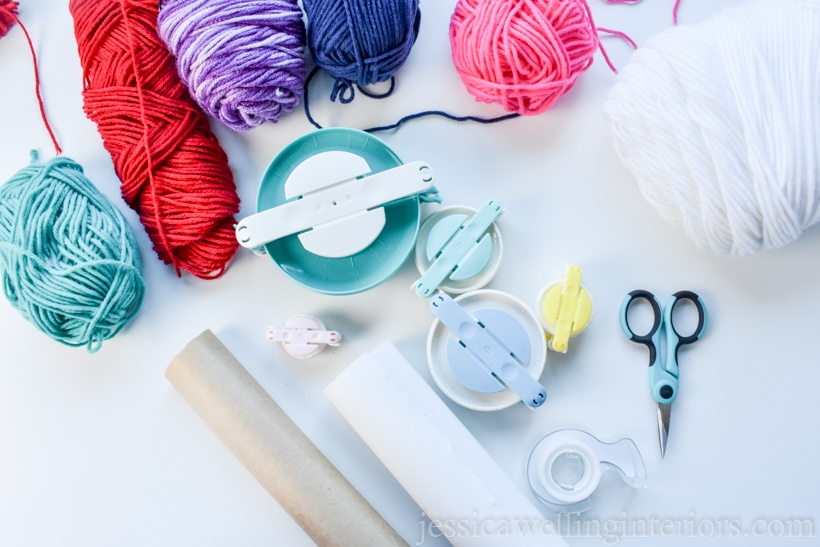 flatlay photo of supplies needed to make pompoms and wrap gifts- colorful arn skeins, pom pom makers in 5 different sizes, tape, craft scissors, and wrapping paper