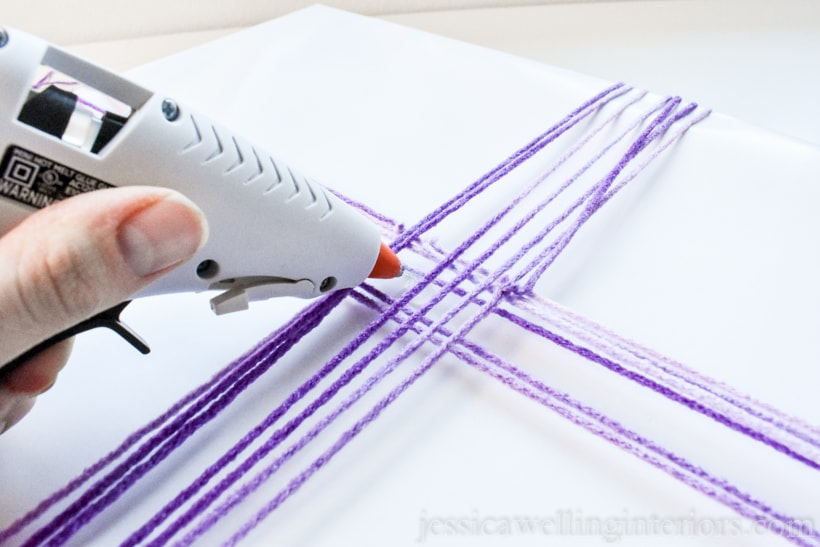 hand holding hot glue gun- applying glue to gift wrapped with white paper and tied with purple yarn