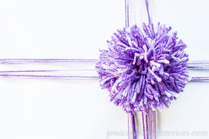 close-up of white wrapped gift tied with purple yarn and a giant purple pom pom