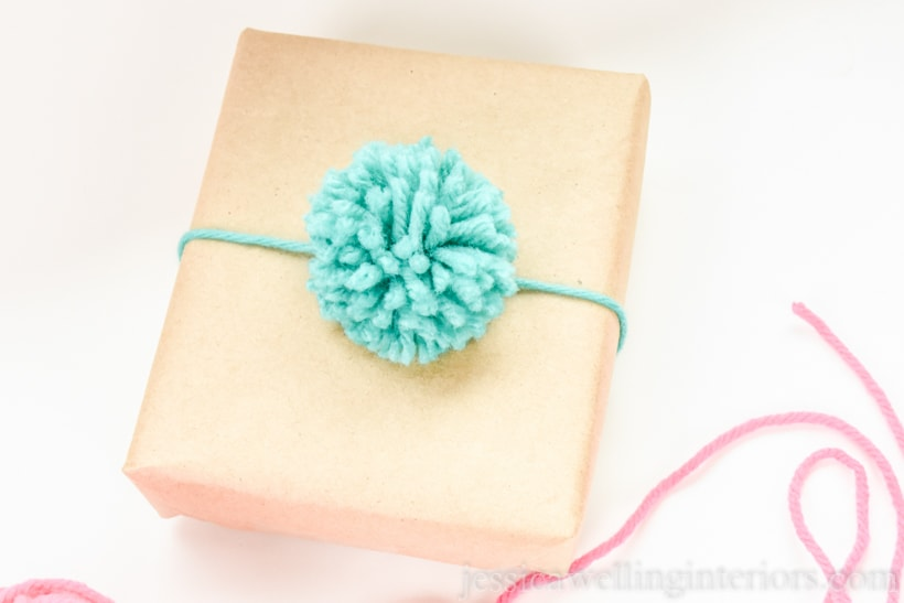 small brown paper parcel tied with aqua-colored yarn and a matching pompom
