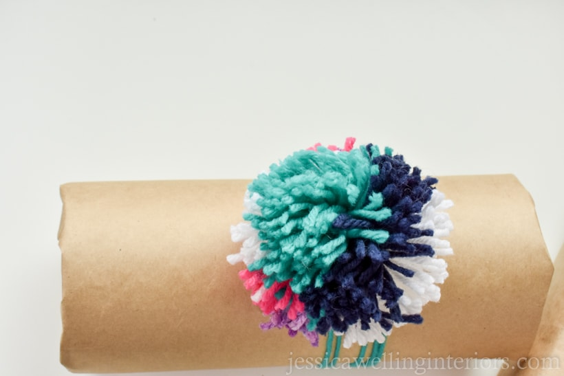 cylider-shaped gift wrapped in brown craft paper and tied with a large multi-coloed pom pom