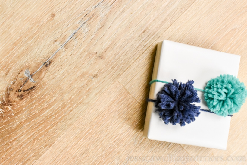 small white paper-wrapped gift with two pom poms on top- one navy blue and one aqua