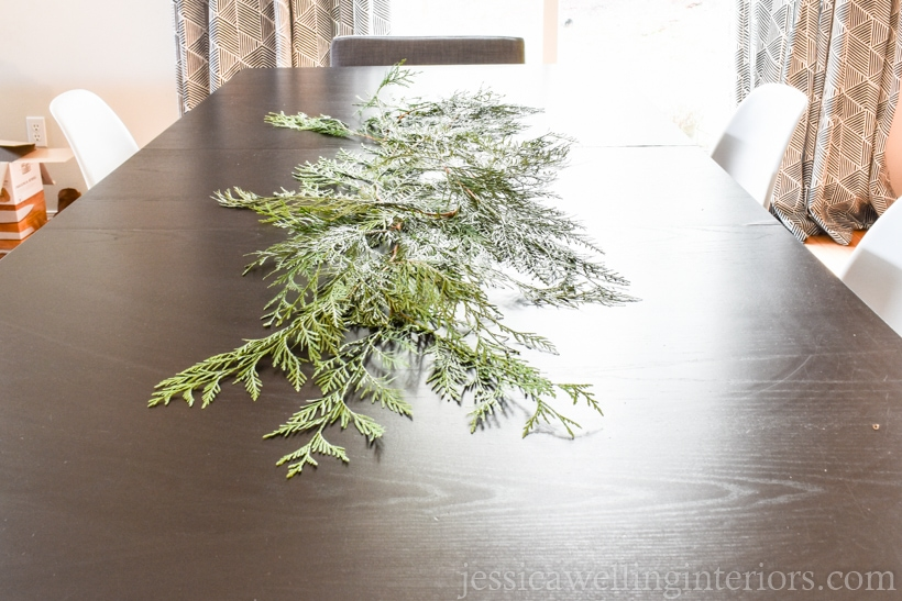 table with evergreen cedar brnaches spread across it