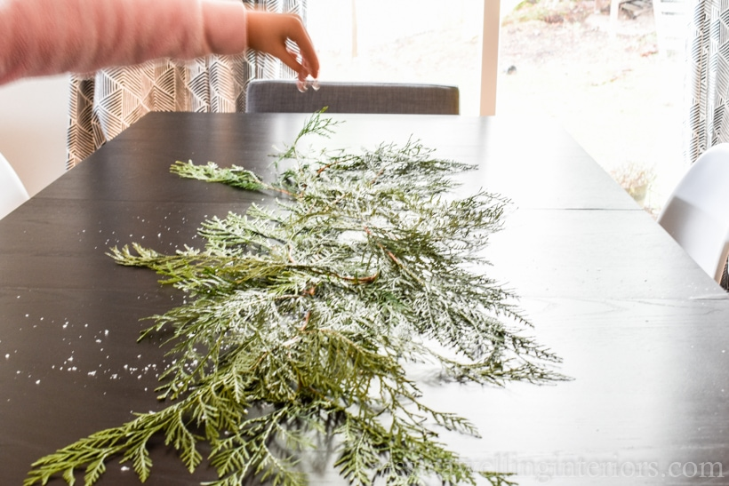 table with cedar branches down the center, and child's hand sprinkling fake snow on them