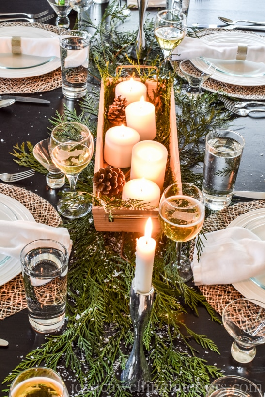 Christmas table decorations with simple cedar branches and a wood tray of candles and pinecones as a centerpiece