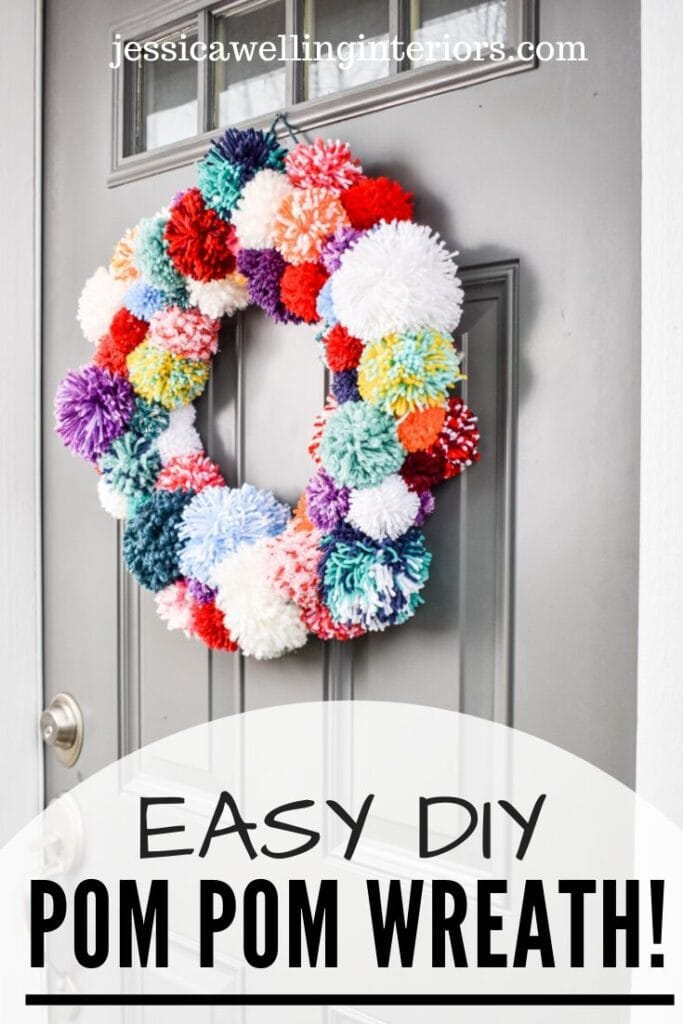 Easy DIY Pom Pom Wreath!: multi-colored wreath made of yarn pom poms on a front door for Christmas