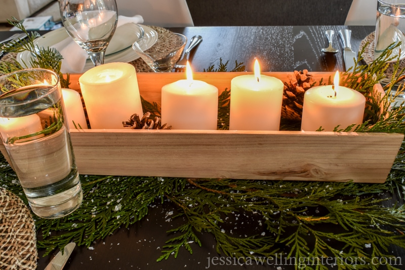 Christmas table decorations with wood tray full of white pillar candles and pine cones
