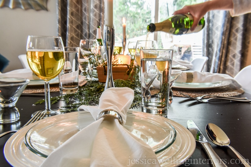 Christmas table setting with hand pouring sparkling cider into a glass