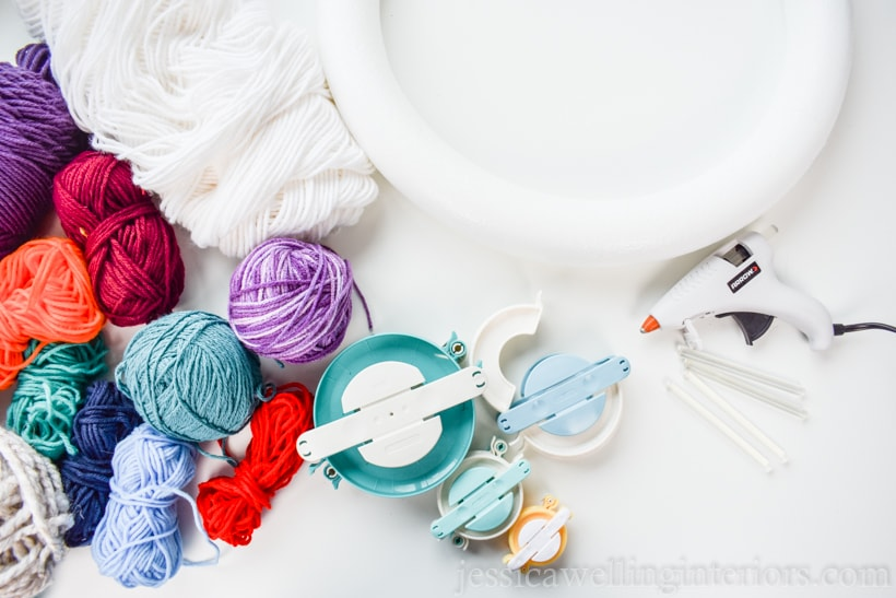 supplies to make a Christmas pom pom wreath- styrofoam wreath form, coored yarn skeins, pom pom makers in varieous sizes, and a hot glue gun