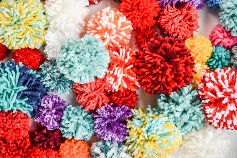 pile of colorful yarn pom poms in a variety of sizes