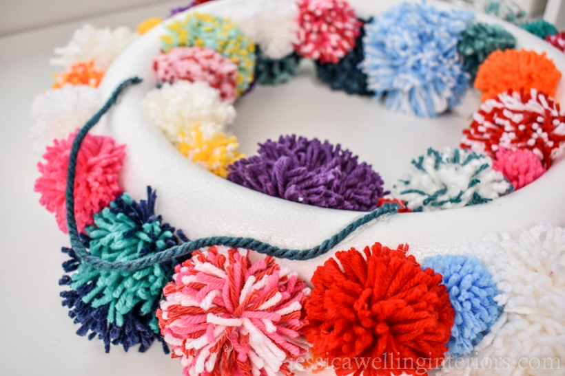back side of pom pom wreath, showing how the hanger yarn is attached to the back of the styrofoam wreath form