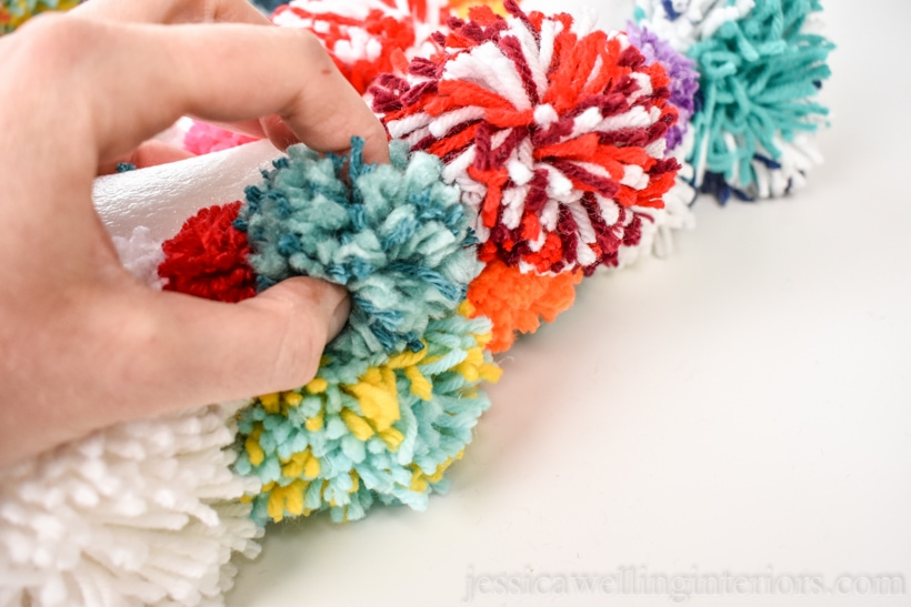 close-up of hand attaching a pompom to the wreath form