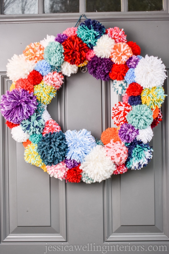 bright and colorful pom pom wreath hanging on a door for Christmas