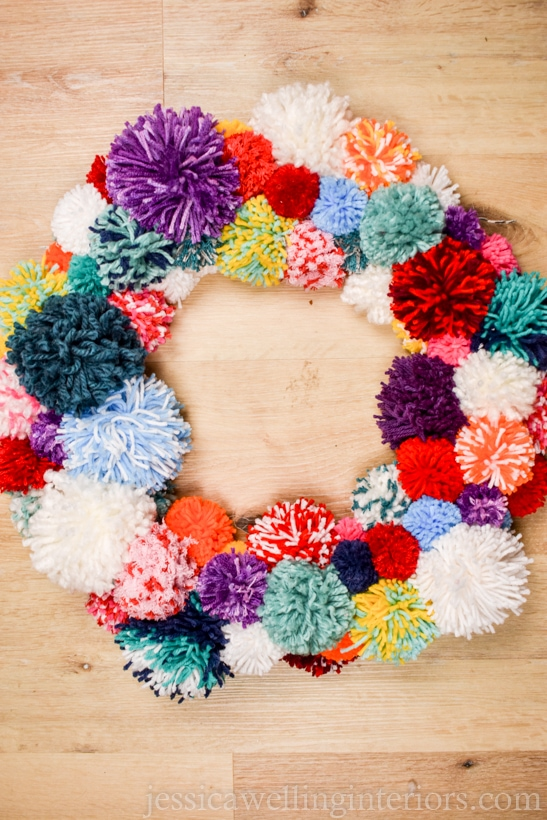 multicolored pompom wreath on a wood background