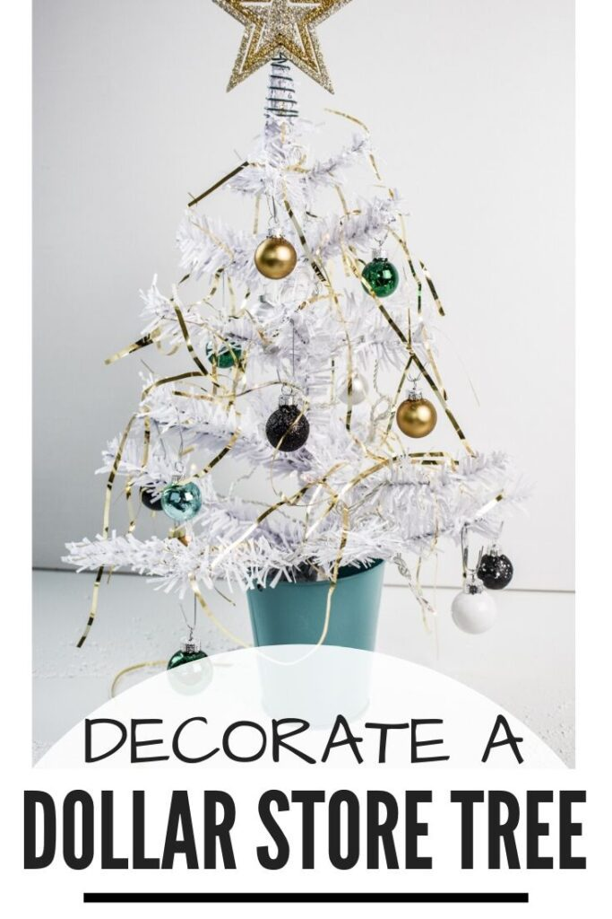 Decorate a Dollar Store Tree: close-up of mini Christmas tree from Dollar Tree, with white flocking, mini ball ornaments, and gold tinsel