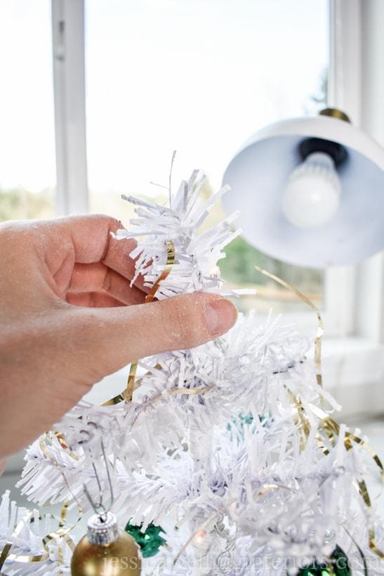 hand adding tinsel to a mini Christmas tree