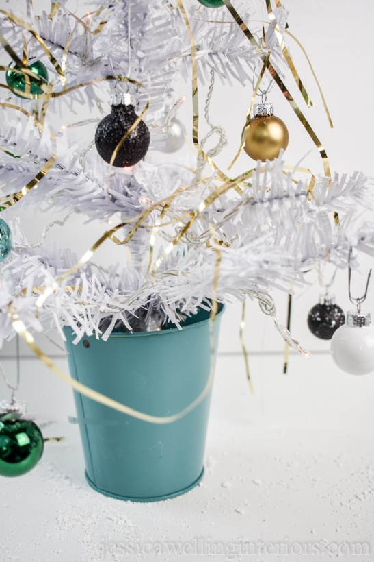 close-up of white dollar store mini Christmas tree decorated with gold tinsel and mini baubles