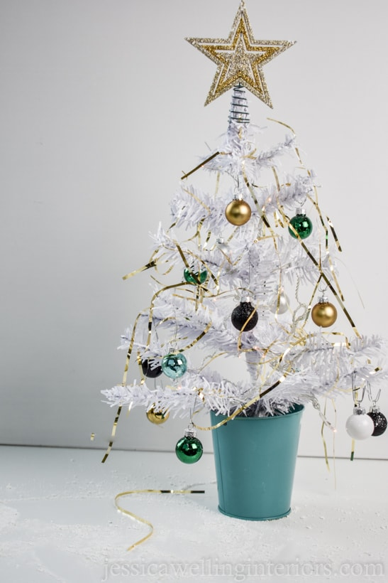 white mini Christmas tree with glam tinsel, lights, and baubles