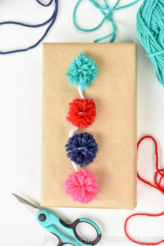 close-up of small parcel wrapped with brown paper and topped with a string of colorful mini pom poms