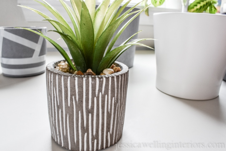 small concrete planter with a faux plant sitting on a white desk