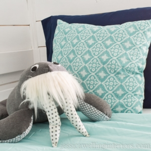 stuffed walrus sitting on an aqua-colored bunk bed