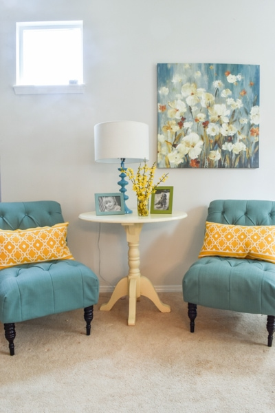 living room with two teal chairs, bright yellow throw pillows, and a colorful painting