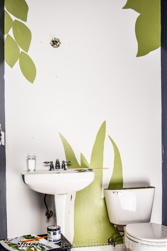 powder room wall painted white, with green leaves and grass to begin a hand-painted botanical mural