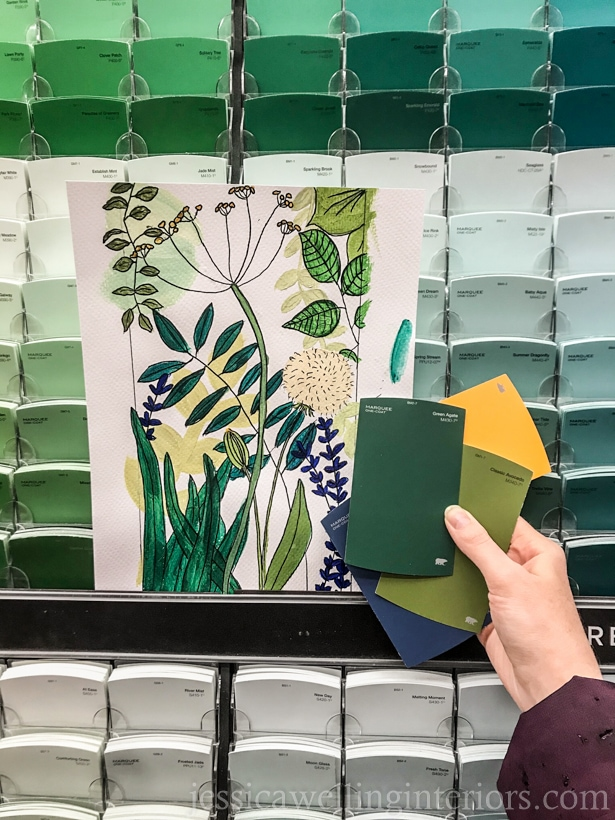 hand drawn and painted botanical art held up in front of paint swatch rack at Home Depot, with hand holding several paint swatchws in greens, yellow, and blue