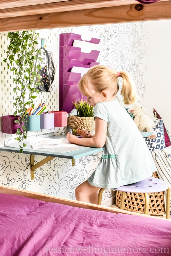 little girl working at a desk in a room with white painted walls and bright colored accessories- the best paint for dark rooms is white