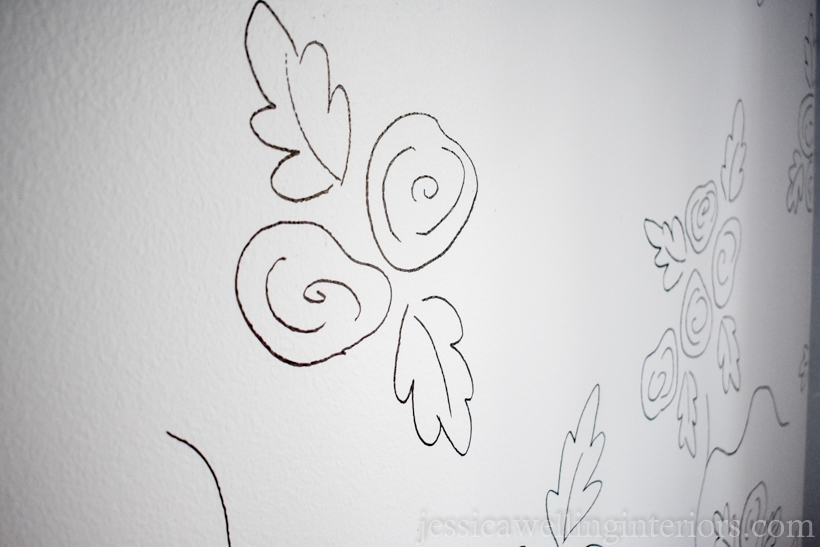 white wall with large roses drawn in black lines to resemble wallpaper