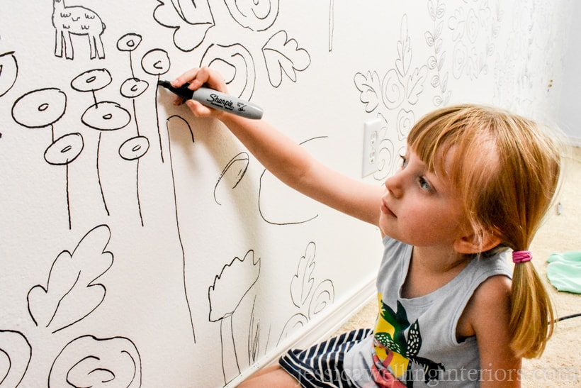 child drawing a pattern on the wall with a Sharpie to create a faux wallpaper accent wall
