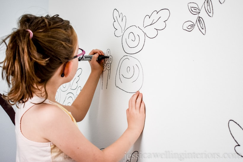 little girl drawing on walls with a black marker to create floral DIY wallpaper