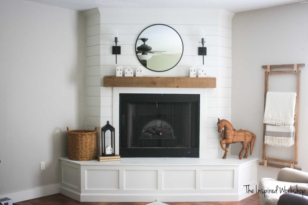 view of living room fireplace, brightened up with white paint and a large mirror above the mantel