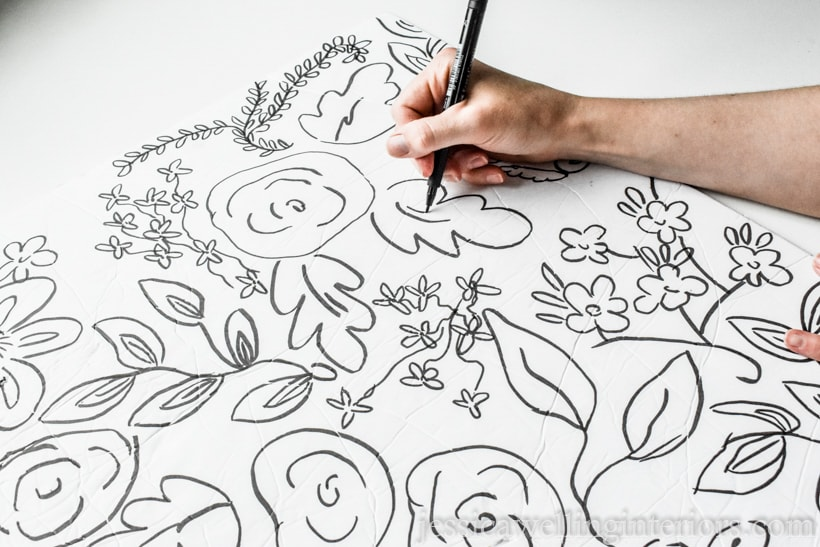 hand drawing whimsical floral pattern on tag board with  black marker to design diy wall art