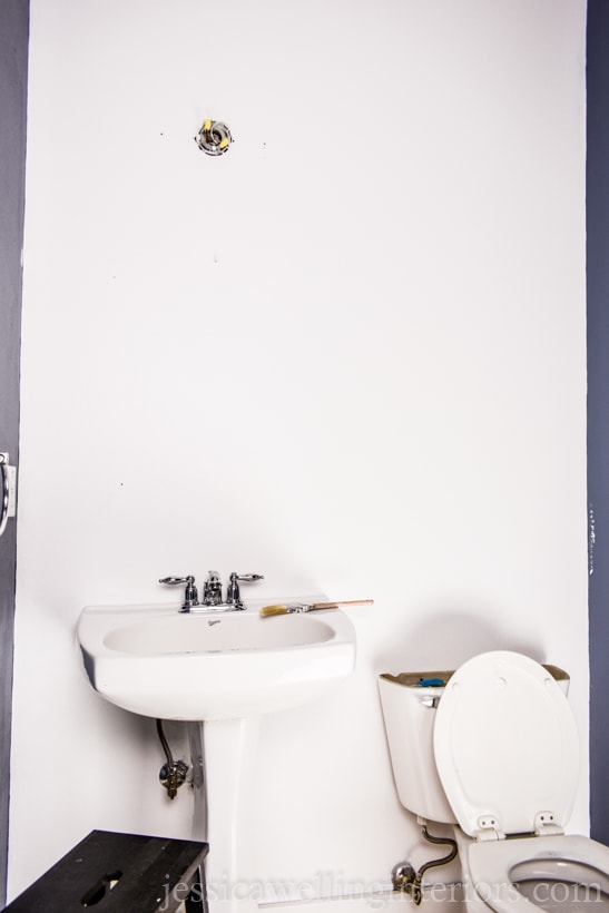 powder room with wall painted Polar Bear white from Behr in preparation for a feature wall mural