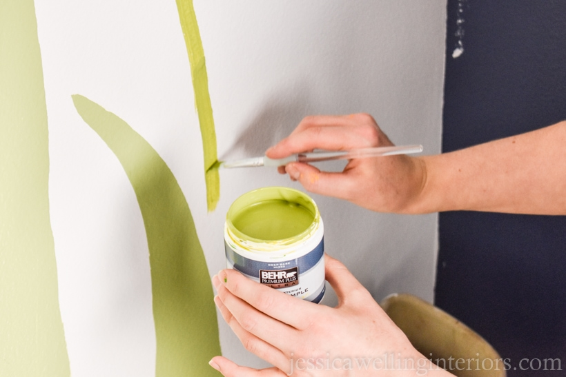hand painting green stems on a  white wall to show how to paint a mural